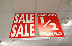 Sale half price shop signs. Photo of sales signs hanging from ceiling of a shop during sale season Royalty Free Stock Image