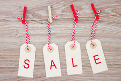 Sale hanging tags. Set of four sale tags hanging on wooden background Stock Photography