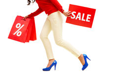 Sale haste. Legs of lady with red paper bags and sale card in move Stock Photography
