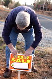 Sale home self. Man putting for sale sign up for home Stock Photo