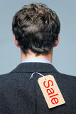 Sale label on the back of a mans jacket. Rear view of a male wearing a suit jacket with a Sale label on it stock photography
