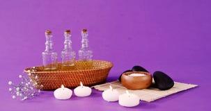 Sale marino in ciotola, ciottoli, olio, candela e fiori di legno stock footage