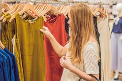 Sale, mode, consumerism och folkbegrepp - lycklig ung kvinna med shoppingpåsar som väljer kläder i galleria eller royaltyfri foto