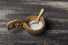 Sale nella cantina del sale e cucchiaio su una tavola di legno Immagini Stock Libere da Diritti