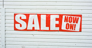Sale now on. A sign on the wall of a wooden shop reading, ' Sale now on ' in bold red and white lettering Stock Photography