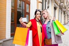 Sale och turism, lyckligt folkbegrepp - härliga kvinnor med shoppingpåsar, gör selfiefotoet Royaltyfri Bild