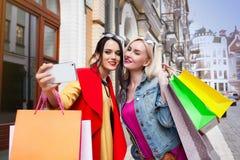 Sale och turism, lyckligt folkbegrepp - härliga kvinnor med shoppingpåsar, gör selfiefotoet Royaltyfri Foto