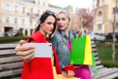 Sale och turism, lyckligt folkbegrepp - härliga kvinnor med shoppingpåsar, gör selfiefotoet Royaltyfria Foton