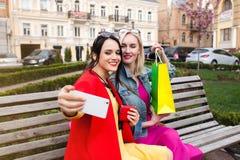 Sale och turism, lyckligt folkbegrepp - härliga kvinnor med shoppingpåsar, gör selfiefotoet Arkivbild