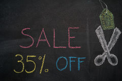 Sale 35% off on chalkboard. Sale 35% off. Sale and discount price sign with scissors cutting price tag drawn with chalk on blackboard Royalty Free Stock Photos