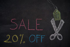 Sale 20% off on chalkboard. Sale 20% off. Sale and discount price sign with scissors cutting price tag drawn with chalk on blackboard Royalty Free Stock Photos