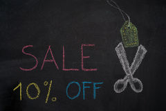 Sale 10% off on chalkboard. Sale 10% off. Sale and discount price sign with scissors cutting price tag drawn with chalk on blackboard Stock Photo