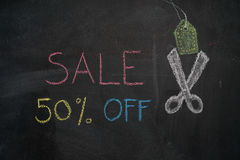 Sale 50% off on chalkboard. Sale 50% off. Sale and discount price sign with scissors cutting price tag drawn with chalk on blackboard Stock Photo