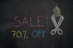 Sale 70% off on chalkboard. Sale 70% off. Sale and discount price sign with scissors cutting price tag drawn with chalk on blackboard Royalty Free Stock Photo