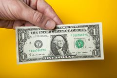 Sale, one dollar in hand on a yellow background stock photos