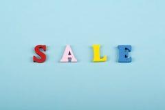 Sale ord på blå bakgrund som komponeras från träbokstäver för färgrikt abc-alfabetkvarter, kopieringsutrymme för annonstext lära Arkivbilder