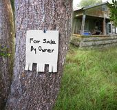 For sale by owner. A sign pinned onto a tree declares the as is home is for sale by owner.  Concept for housing market in bad times or during foreclosures Royalty Free Stock Photos