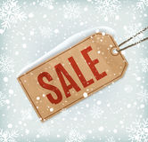 Sale paper tag on background with snowflakes and Stock Photos