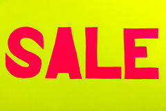Sale papper undertecknar in rött på en gul bakgrund Arkivfoto