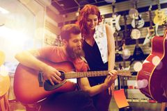 Couple of musicians playing guitar at music store Royalty Free Stock Image