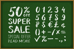 Sale 50 percent drawing on blackboard. Numbers 0-9 written with a brush on a black background lettering. Super Sale. Big sale. Sal Royalty Free Stock Image