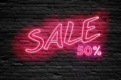 SALE 50 % Percent. fluorescent Neon tube Sign on dark brick wall. Front view. Can be used for online banner ads or background. Stock Image