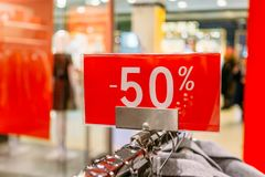 Sale 50 percent off letters on red banner inside popular fashion store. With blurred mall background. Discount and sale time in shops concept Stock Photo