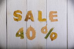 Sale 40 percent. The text `sale, 40 percent` cut from different yellow and orange fallen leaves from the trees and laid on the white wooden boards Royalty Free Stock Image