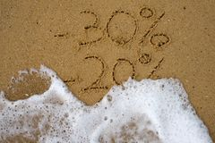 Sale percents drawn on sand. Royalty Free Stock Photos