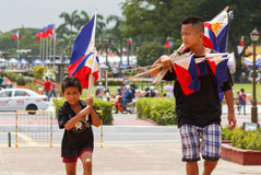 For sale Philippine flag. Metro Manila, Philipines - June 12, 2012: This youngster were selling the national flag of the Philippines at Luneta Park nearby stock images