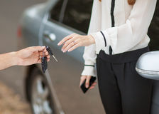 Sale / purchase of the vehicle. Male hand giving car key to female hand. She is holding a cell phone. In the background, a fragment of the car Stock Image