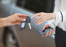 Sale / purchase of the vehicle. Male hand giving car key to female hand. She is holding a cell phone. In the background, a fragment of the car Royalty Free Stock Photo
