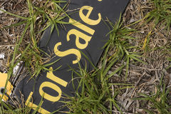 For Sale Real Estate Board. Real Estate Black and Yellow For Sale board laying between grass growing and dying Stock Photography
