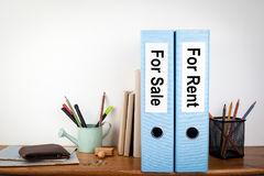 For sale and rent binders in the office. Stationery on a wooden shelf.  Stock Images