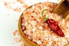 Sale rosa dall'Himalaya su fondo bianco Mucchio di sale himalayano rosa Sale e peperoncini Vendita delle spezie immagini stock