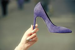 Sale in the shoe. glamour shoe blue color suede on female hand. On blurred background, fashion and beauty, shopping and presentation, cinderella Royalty Free Stock Photos