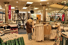 Sale. Shopping. A woman shopping for clothes in a mall having a sale Royalty Free Stock Photos