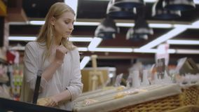 Sale, shopping, consumerism and people concept - happy young woman choosing and reading label on bread in market. stock video