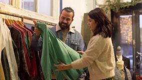 Couple choosing clothes at vintage clothing store stock footage