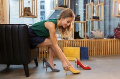 Young woman trying high heeled shoes at store stock images