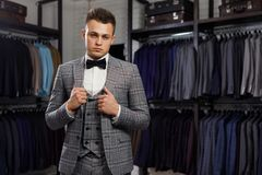 Sale, shopping, fashion, style and people concept - elegant young man choosing and trying jacket on in mall or clothing. Perfect to the last detail. Modern Royalty Free Stock Images