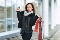 Sale, shopping, tourism and happy people concept - beautiful woman with shopping bags and credit card in the hands on a street. royalty free stock images