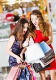 Sale, shopping, turism och lyckligt folkbegrepp - två härliga kvinnor som ser inre shoppingpåsar i shoppa Arkivbild