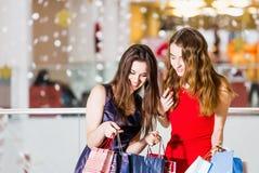 Sale, shopping, turism och lyckligt folkbegrepp - två härliga kvinnor som ser inre shoppingpåsar i shoppa Royaltyfria Bilder