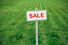 Sale sign against trimmed lawn background. Sale sign against trimmed green lawn background royalty free stock image