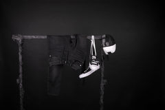Free Sale Sign. Black And White Sneakers, Cap Pant, Jeans Hanging On Clothes Rack Background. Friday. Copy Space. Stock Photos - 80939793
