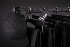 Sale sign. Black cap and pant, jeans hanging on clothes rack   background.   friday.  Close up. Stock Photo