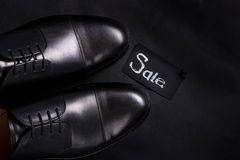 Sale sign. Black oxford shoes on  background. Top view. Copy space. Sale sign. Black oxford shoes on black background. Top view. Copy space Stock Images