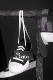 Sale sign. Black and white sneakers, cap  hanging on clothes rack   background.   friday. Close up. Royalty Free Stock Photo