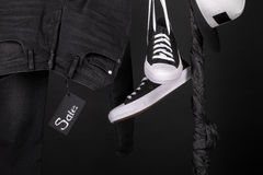 Sale sign. Black and white sneakers, cap  pant, jeans hanging on clothes rack   background.   friday. Close up. Stock Photography
